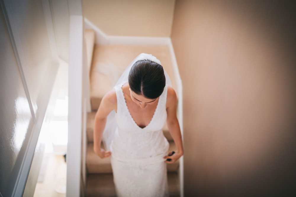 bride walks down the stairs - getting ready to leave to church