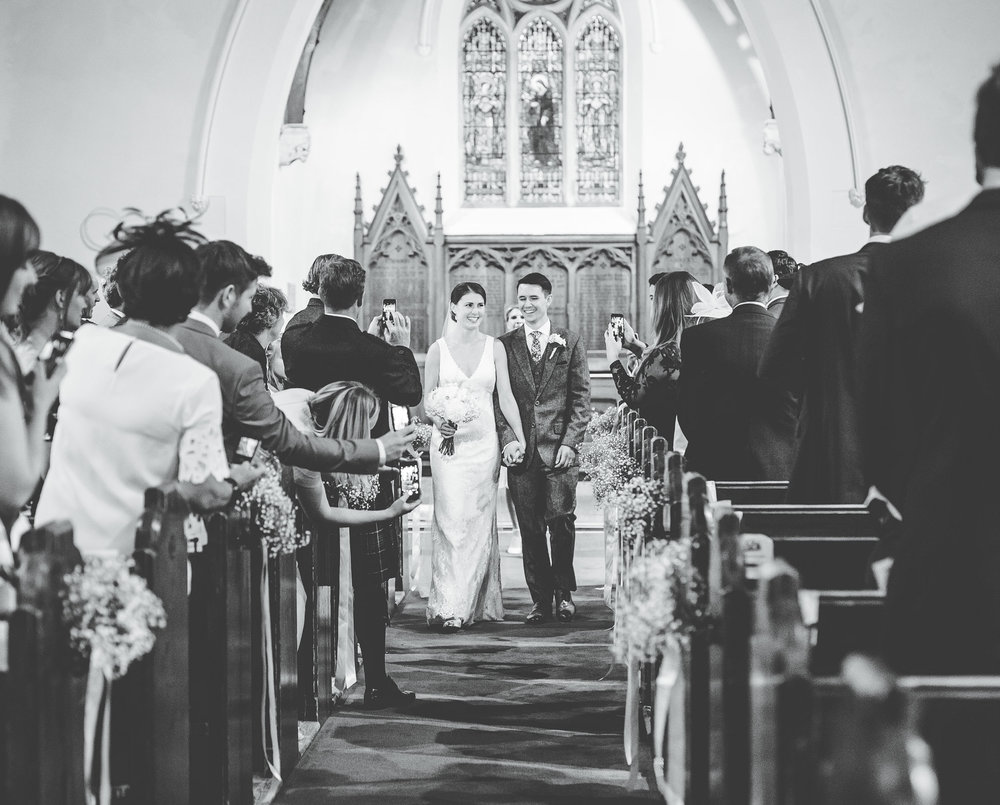 black and white wedding photography - leaving church