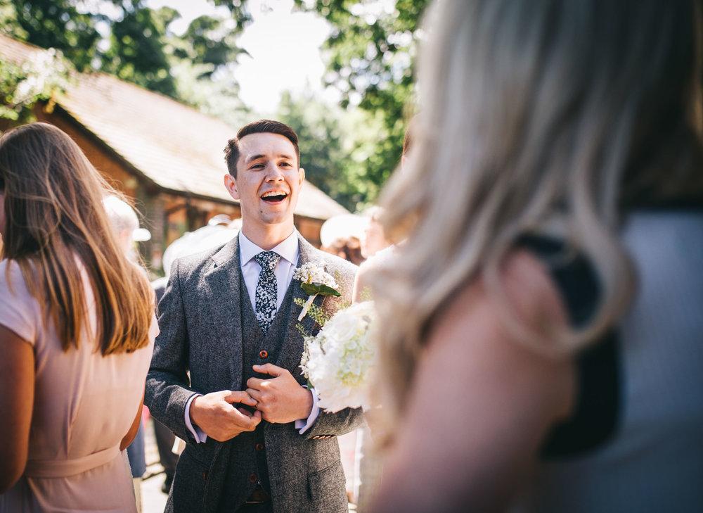 groom laughs outside church - lancashire wedding photography
