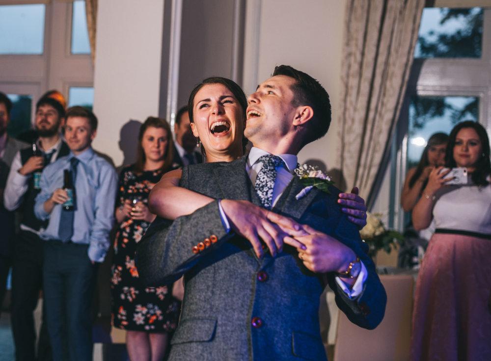 bride and groom laugh during dancing - lancashire wedding venue