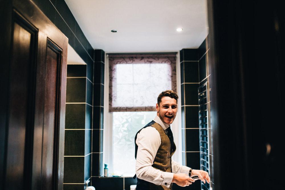 laughing best man during groom prep