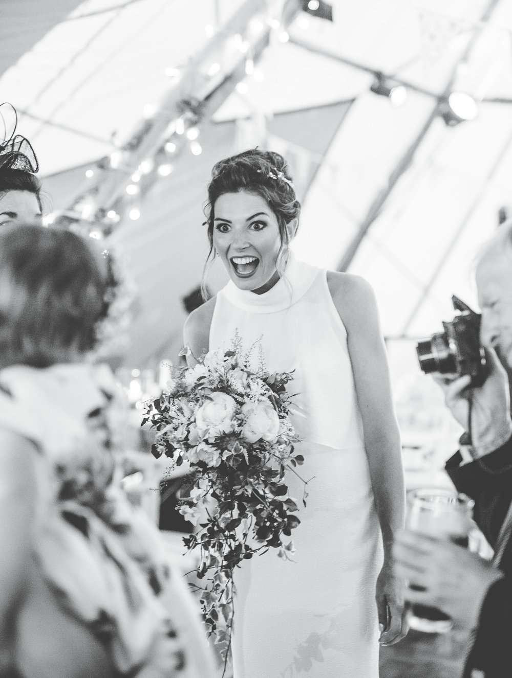 fun and creative wedding photography - bride laughing with guests in the tipi