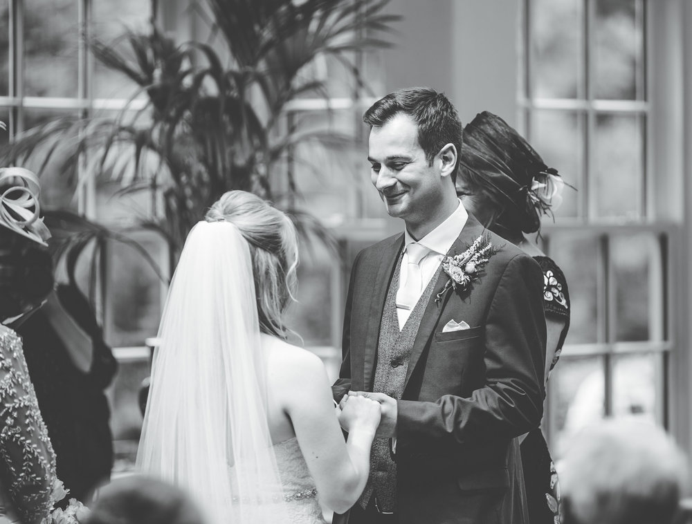 Black and white wedding pictures at Mitton Hall - exchanging the rings