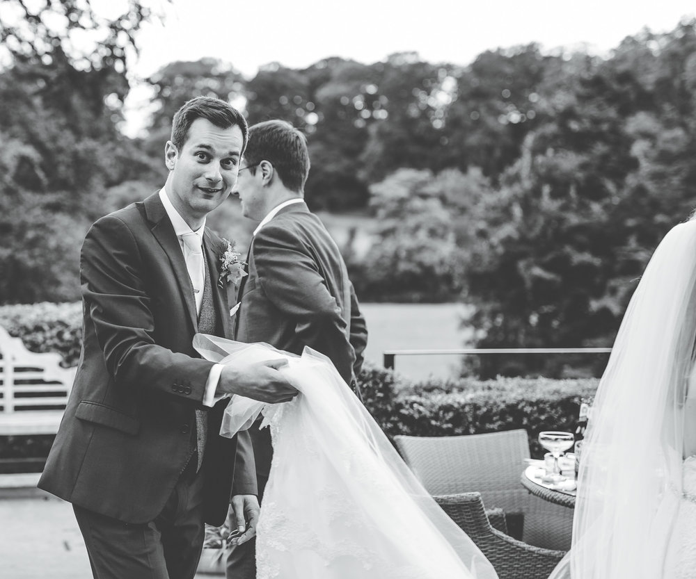 groom carries the bride's dress - fun and quirky wedding photography in Lancashire