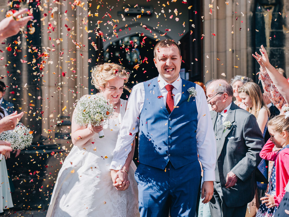 walking through the confetti at Stonyhurst college - smiling bride and groom