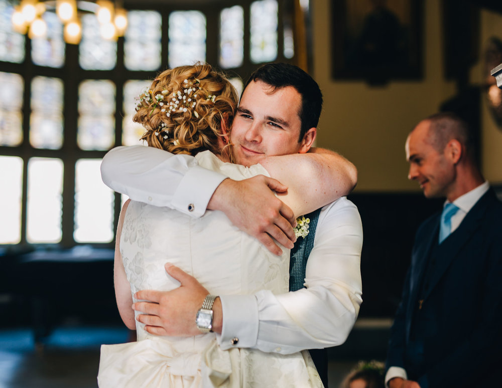 documentary wedding photographer in lancashire - guests hugging the bride