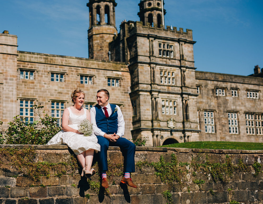 bride and groom sitting outside Stonyhurst college - laughing naturally