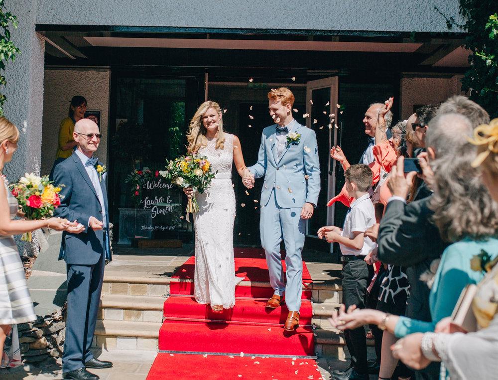 couple walk through the confetti at Swan at Newby Bridge