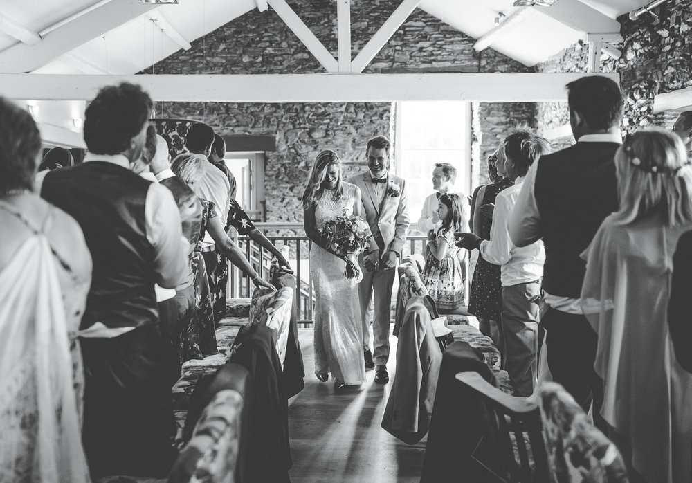 couple walk into their reception at Swan at Newby Bridge
