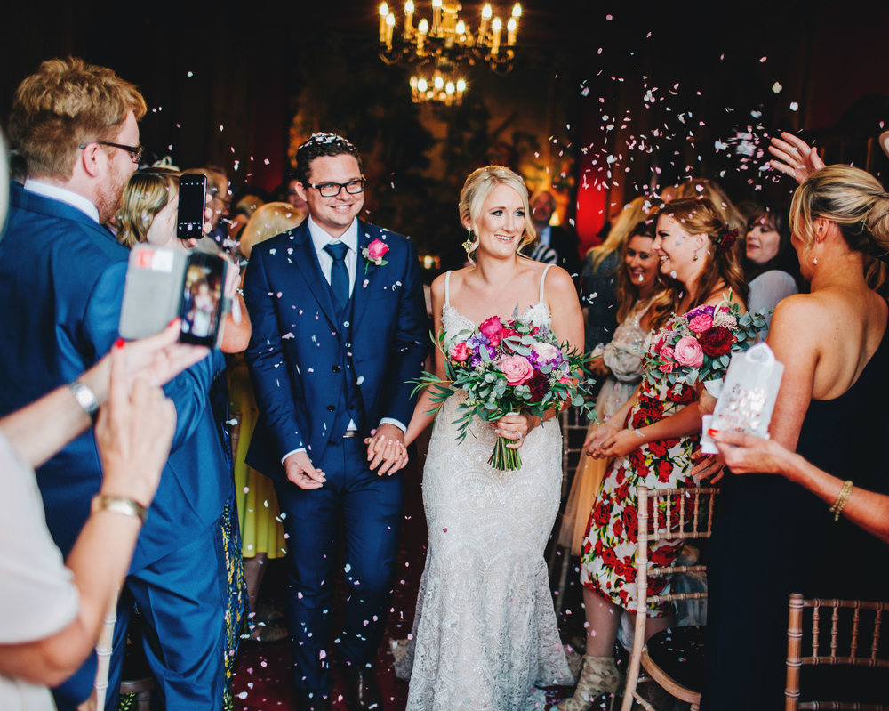couple walk down the aisle through the confetti at Thornton Manor