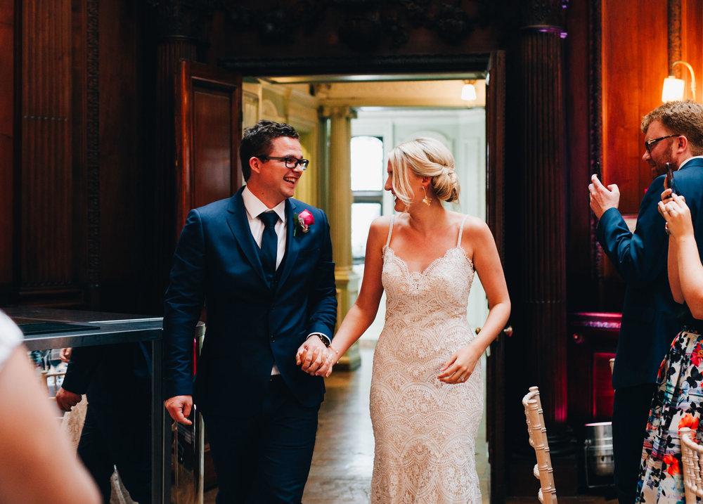 couple laugh as they walk into their wedding breakfast - thornton manor wedding