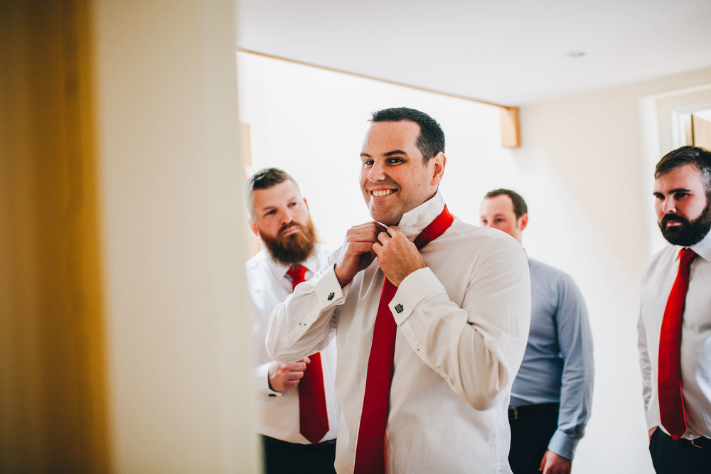 documentary shot of groom laughing