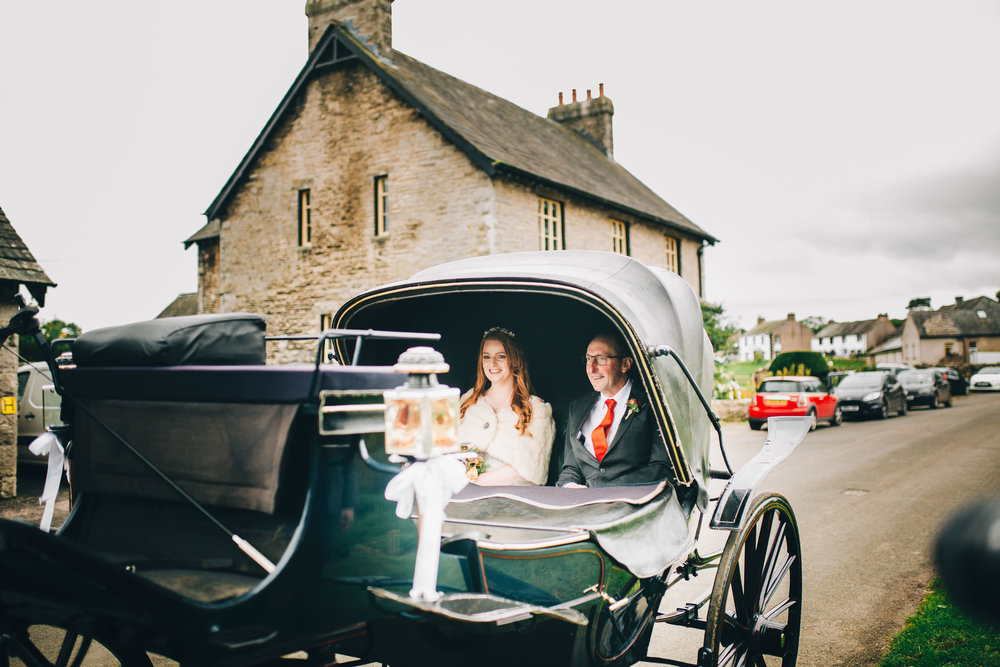 bride arrives at church in horse and carriage