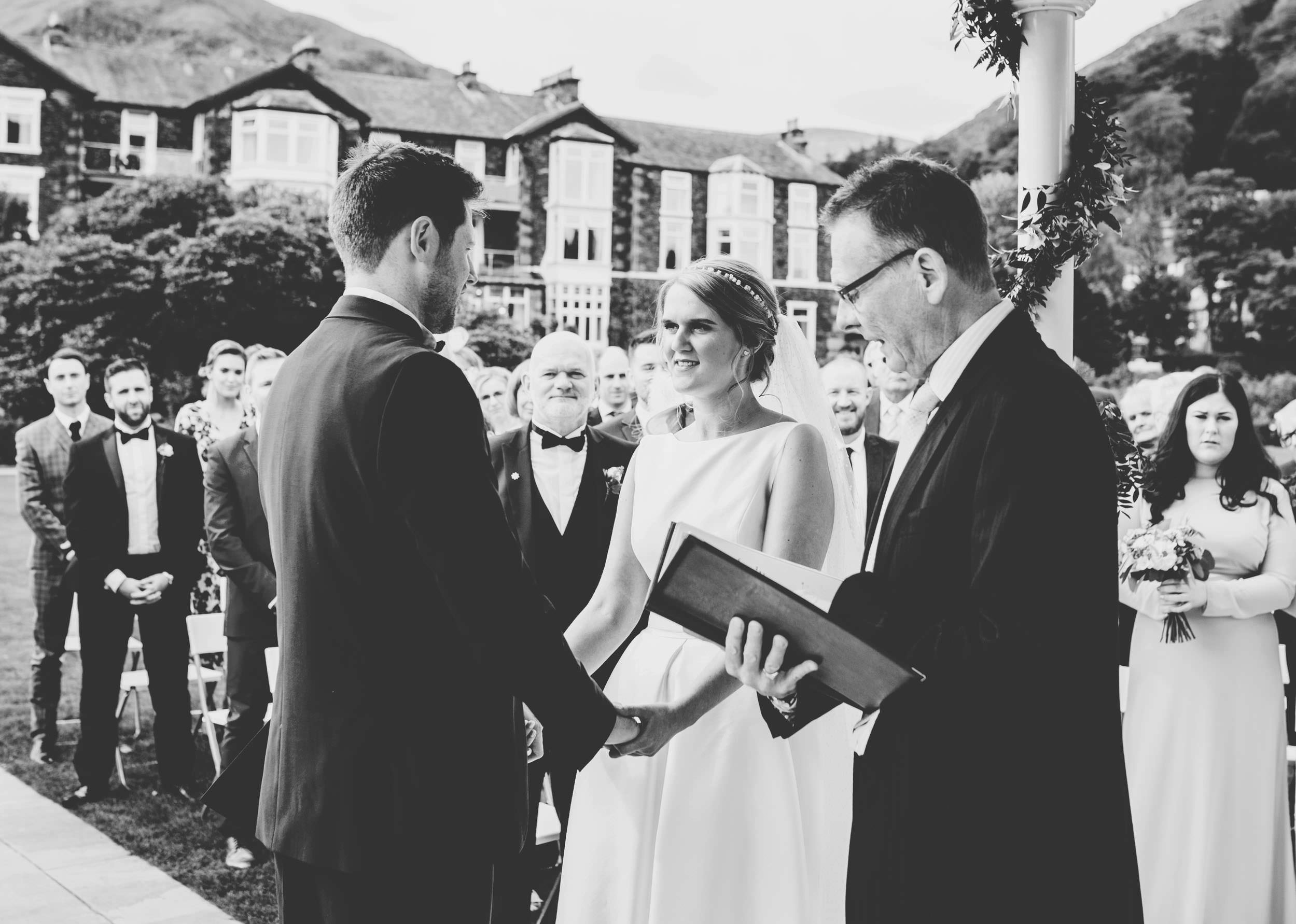 bride and groom laugh during ceremony - Lake District wedding photographer