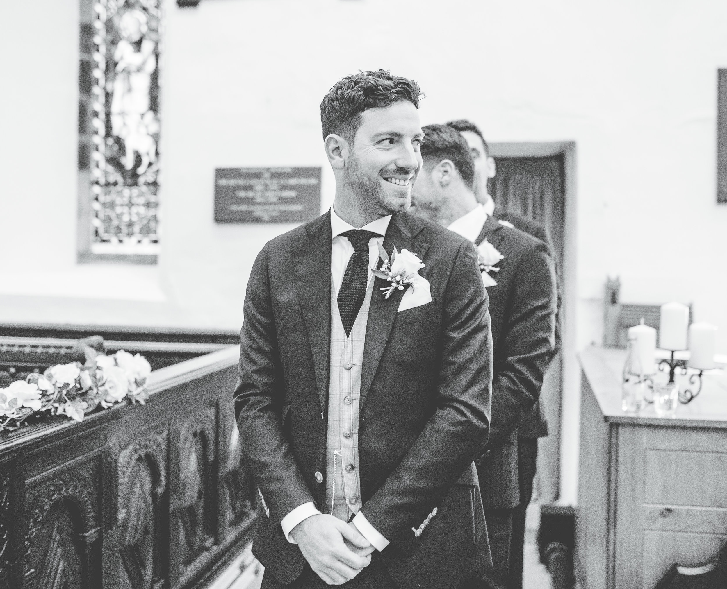 groom watches the bride arrive - documentary wedding photography in the lakes