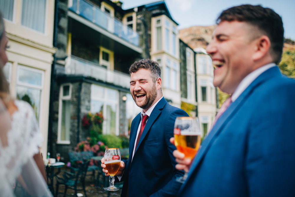 Lake District wedding photography - guests laughing with drinks