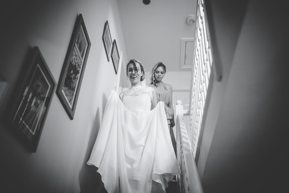 bride walks down the stairs - black and white wedding pictures