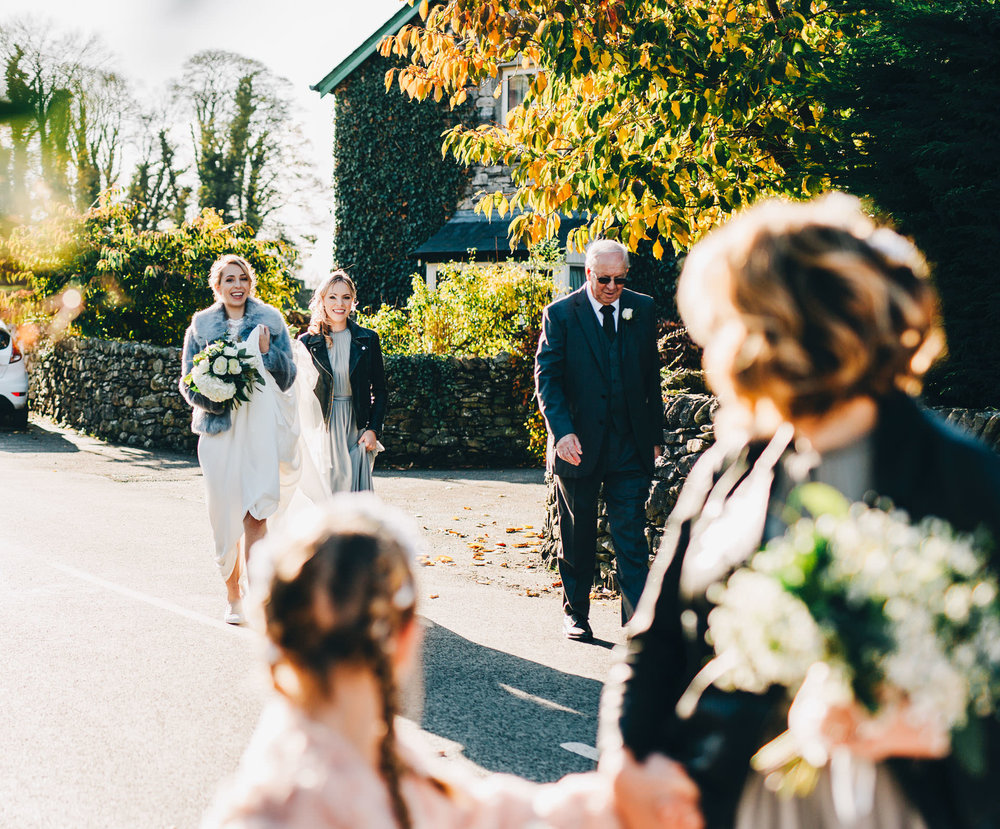 bride walks over the church in the Lake District