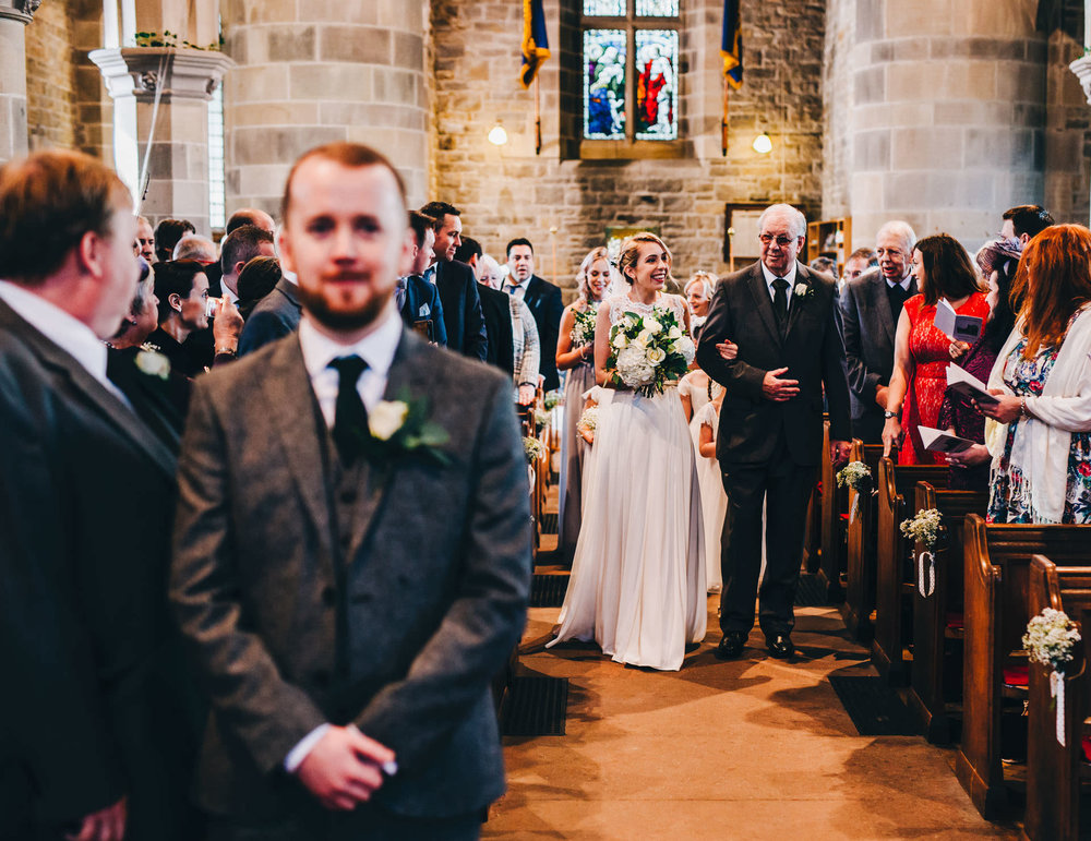 bride walks down the aisle - documentary wedding photography Lake District