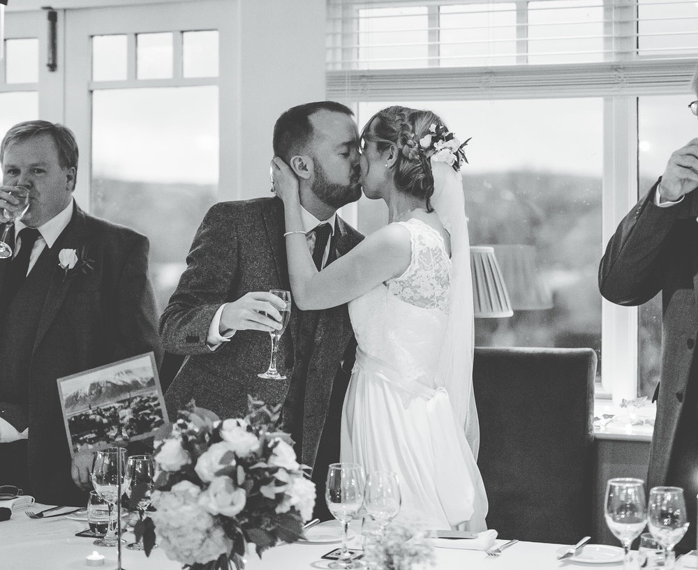 bride and groom kissing at the wedding breakfast