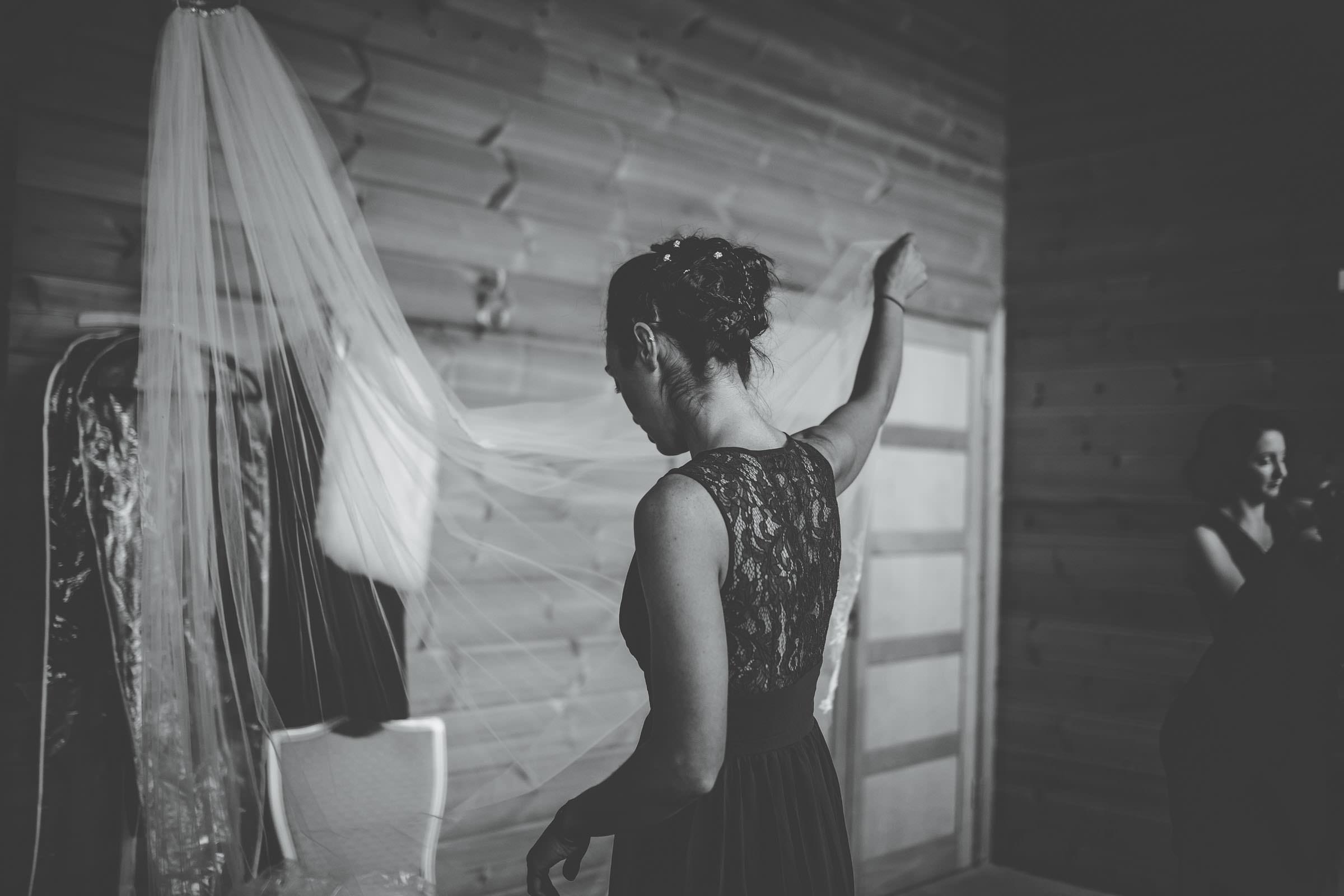 veil bridesmaid holding it up.