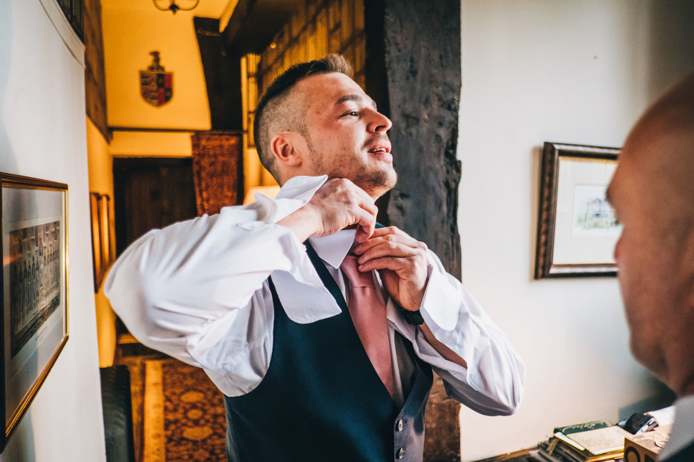 groom getting dressed at home - wedding photography in Cheshire