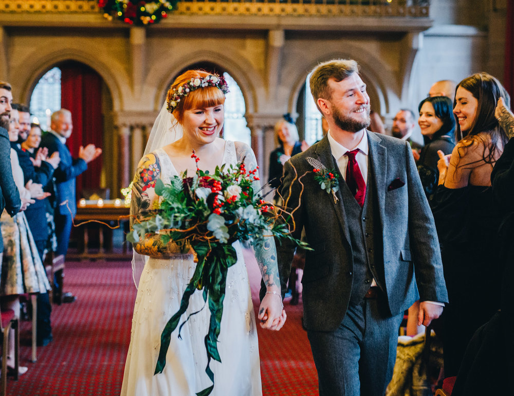 couple walk down the aisle - Manchester town hall wedding