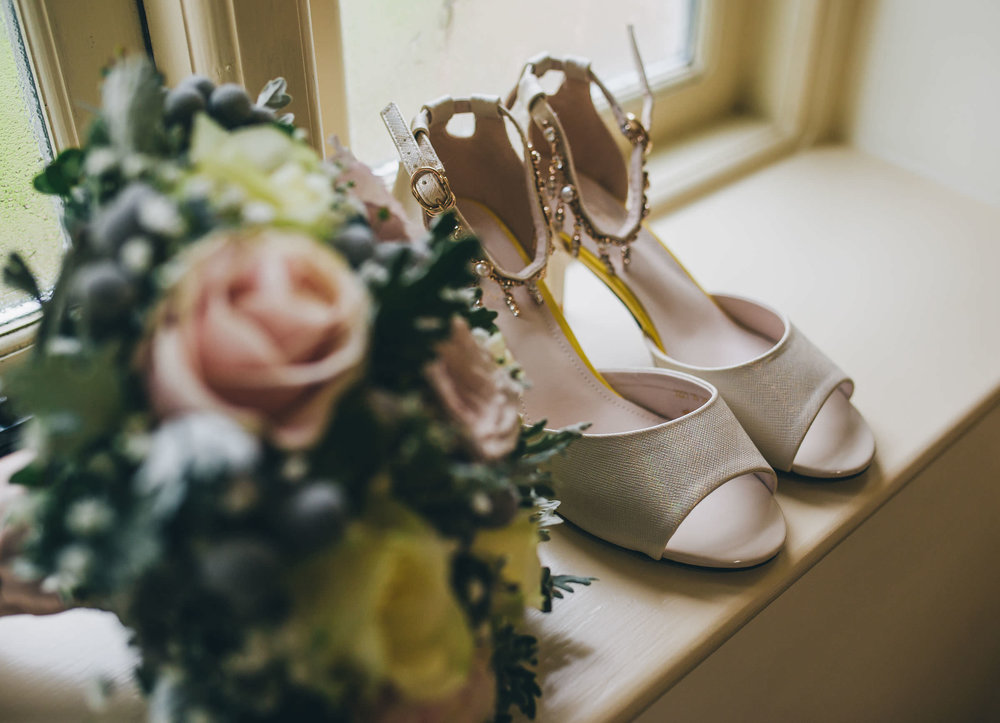 The brides shoes and bouquet. Wedding photographer in Shropshire. Winter wedding photography.