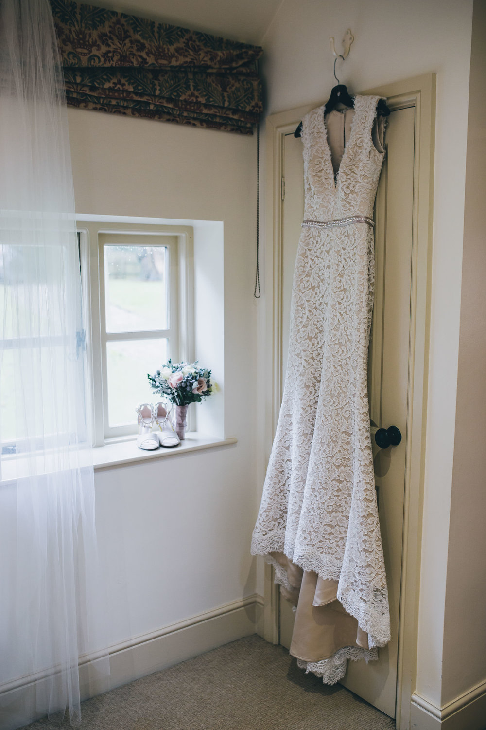 The lace wedding dress hung up. A winter wedding at Combermere Abbey.