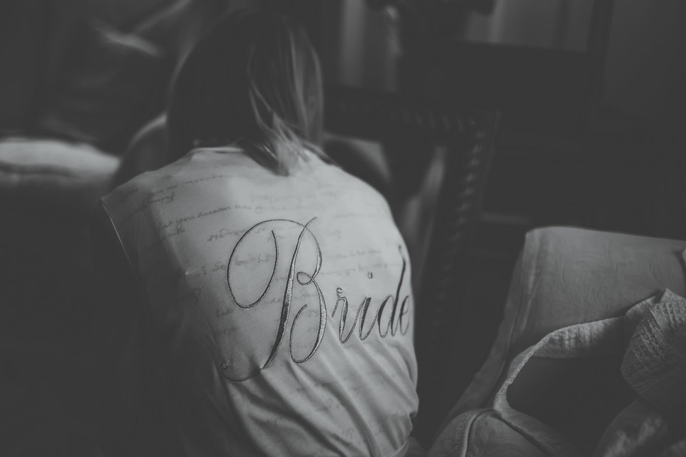 Bride written on the brides dressing gown. A winter wedding at Combermere Abbey. Creative photographer.