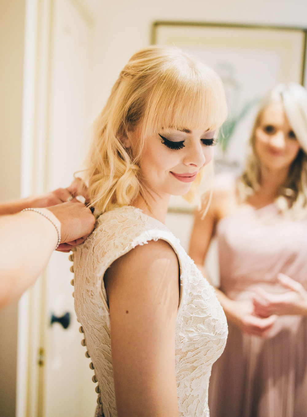 The bride having her dress done up. Documentary styled wedding photographer in Shropshire. Wedding at Combermere Abbey.