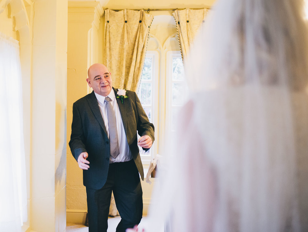 Father of the bride seeing his daughter in her dress. Documentary styled wedding photographer in Shropshire. Combermere Abbey.