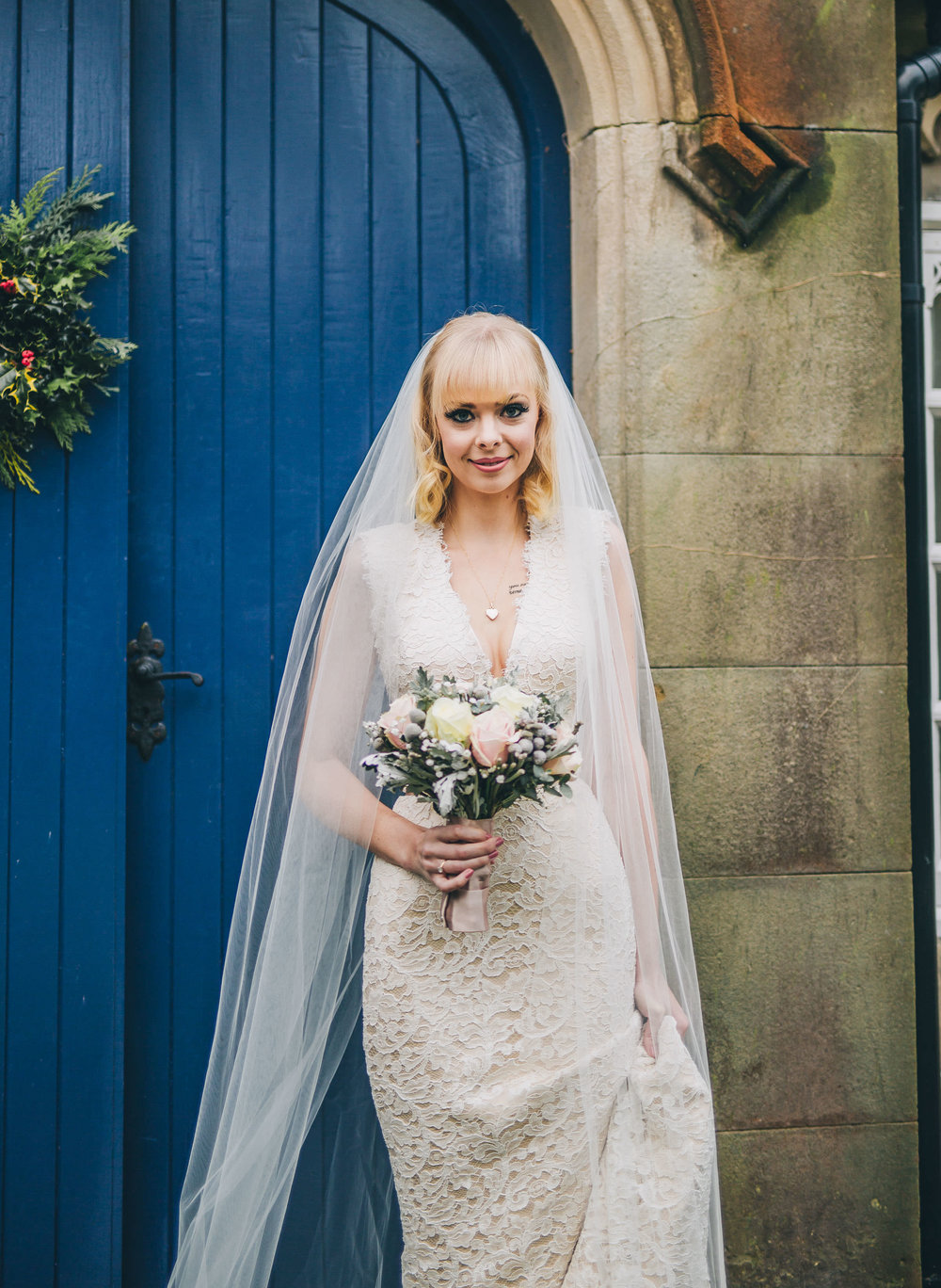 The bride holding her wedding bouquet outside of Combermere Abbey for her winter wedding.