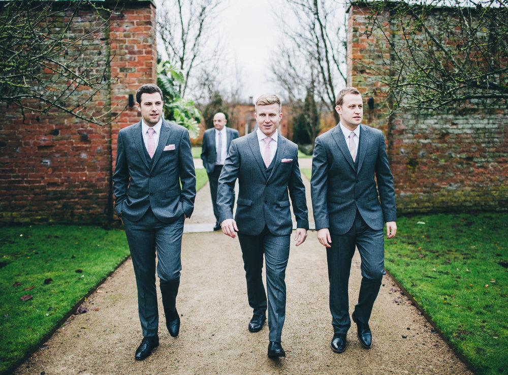 The groom and groomsmen walking up to Combermere Abbey for his wedding. Documentary wedding photographer.