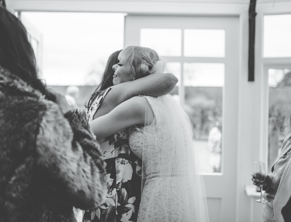 Hugs from wedding guests to the bride. Documentary wedding photographer in Shropshire.