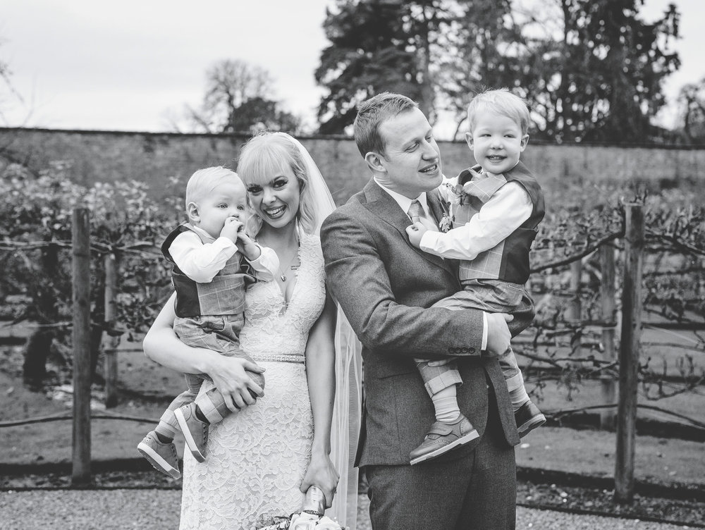 The bride and groom with their little boys. Documentary wedding photographer in Shropshire.
