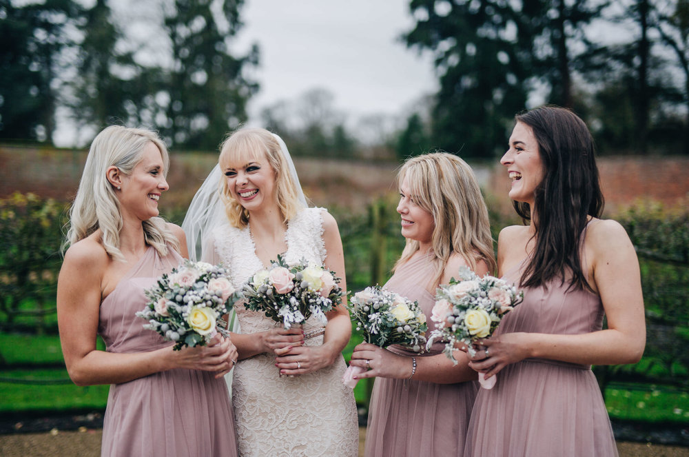 Laughter from the bride and her bridesmaids. Combermere Abbey for a winter wedding.