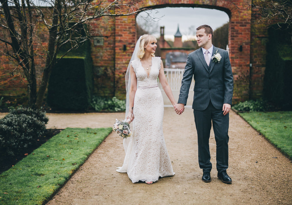 Bride and groom holding hands in Shropshire. Combermere Abbey for a winter wedding.