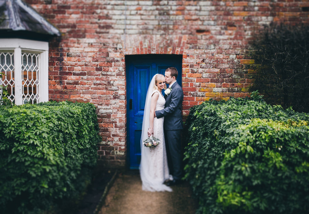 The bride and groom kissing in a blue doorway. Documentary wedding photographer.