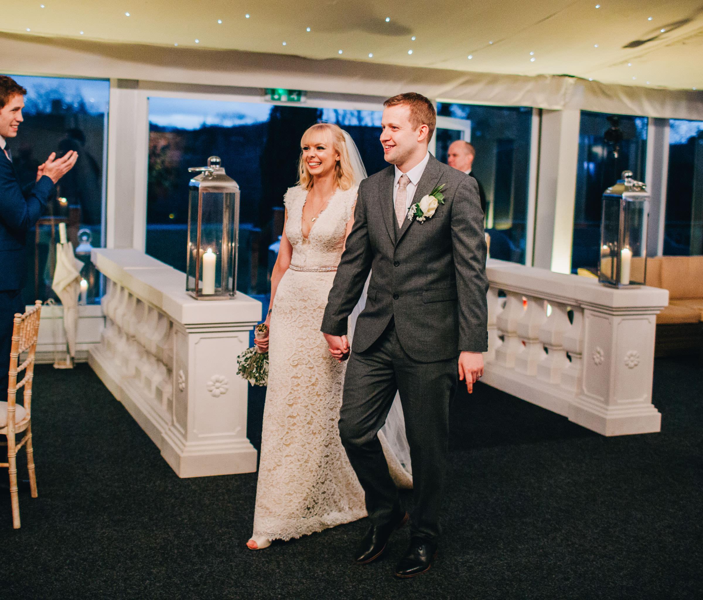 bride and groom walk into the wedding reception