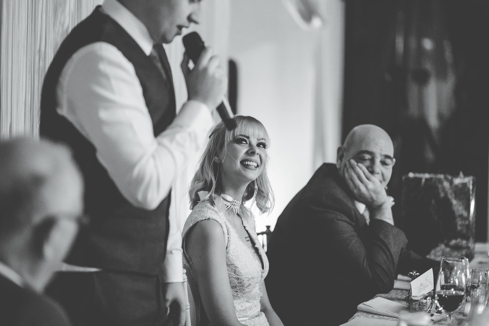 Smiles from the bride during the speeches. Documentary wedding photographer.