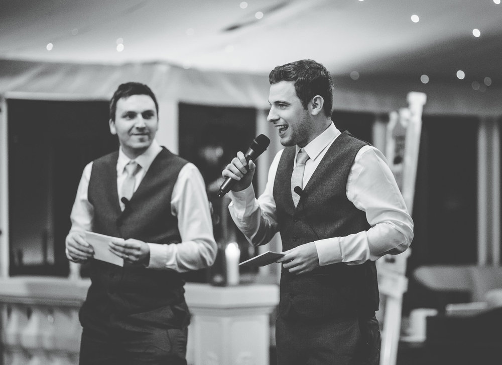Black and white photo of the groom doing his speech. Creative photographer.