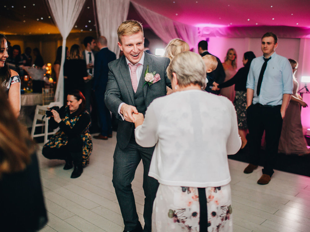Family and friends dancing. Creative wedding photographer.