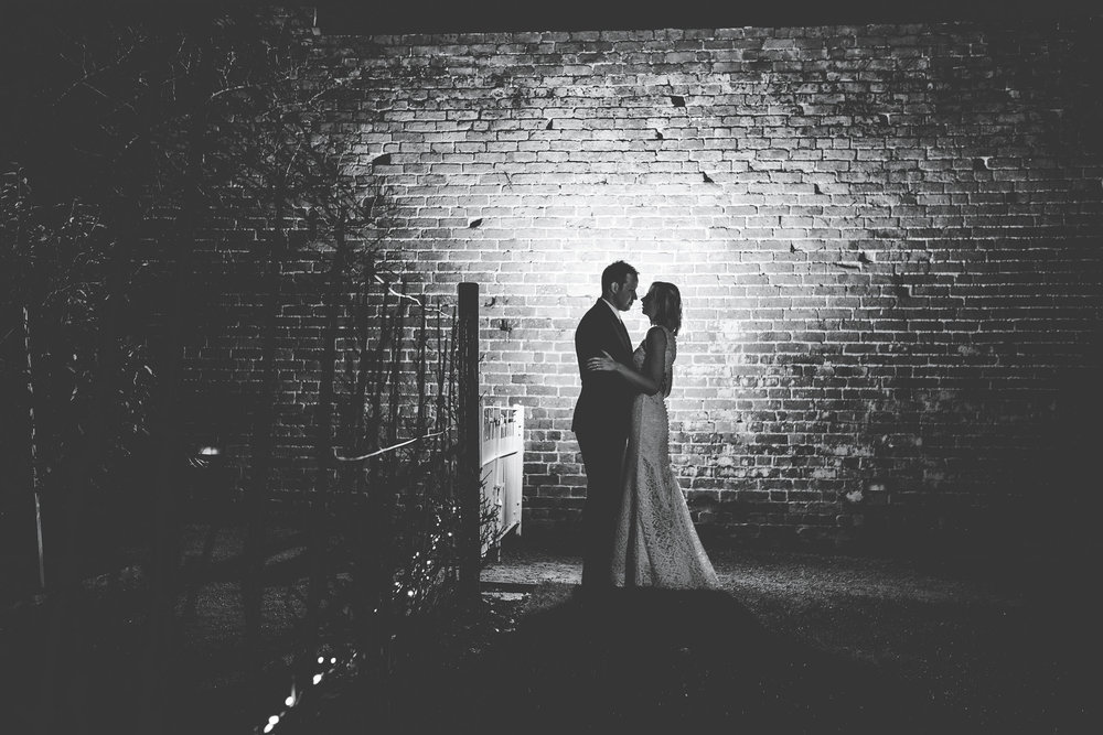 The bride and groom in the dark outside of Combermere Abbey.