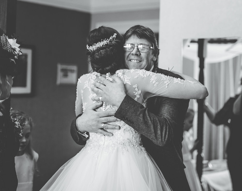 Hugs from the bride and her father. Creative wedding photographer.