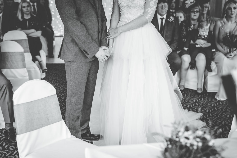 Black and white photo of the bride and groom holding hands during the ceremony.
