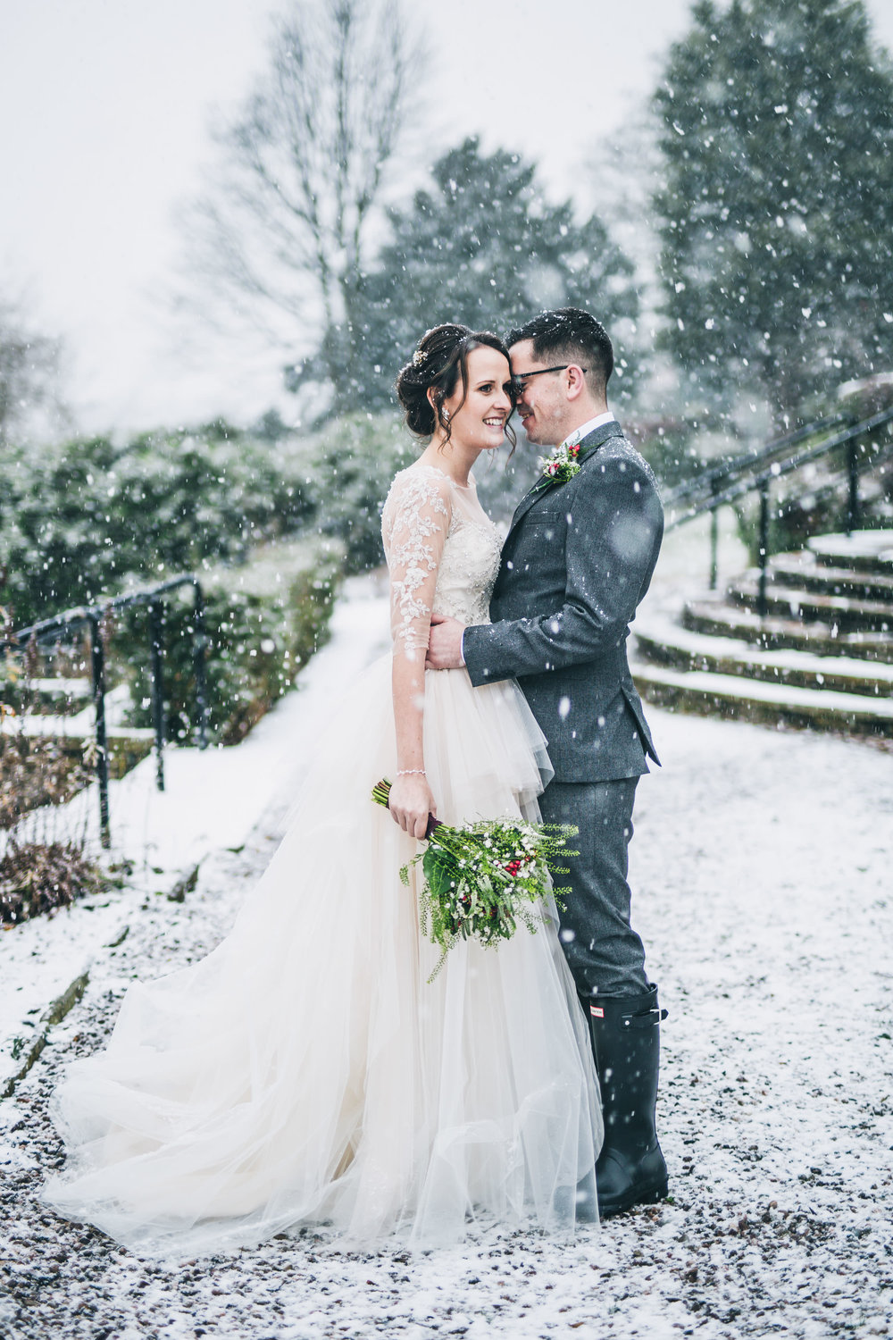 The bride and groom outside. Snowy wedding photos.