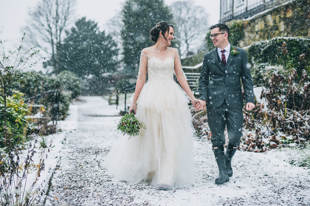 The bride and groom walking in the snow. Snowy wedding photos.