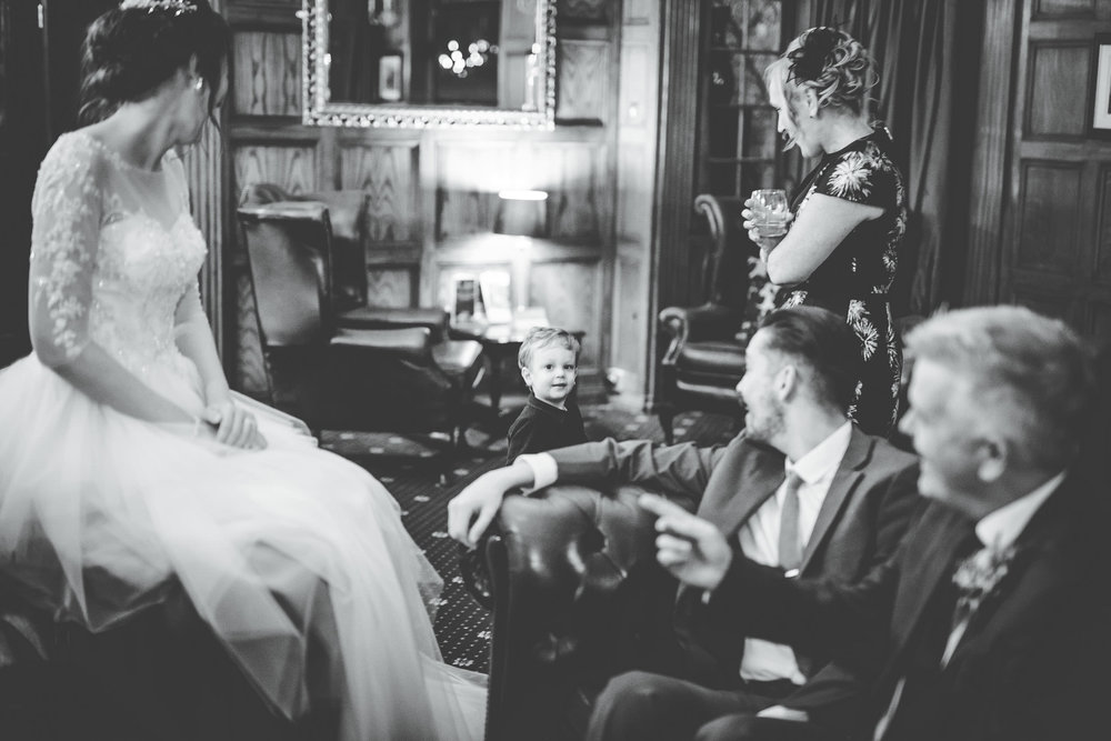 Black and white photo of the bride talking with wedding guest new the fire. Documentary wedding photographer in Lancashire.
