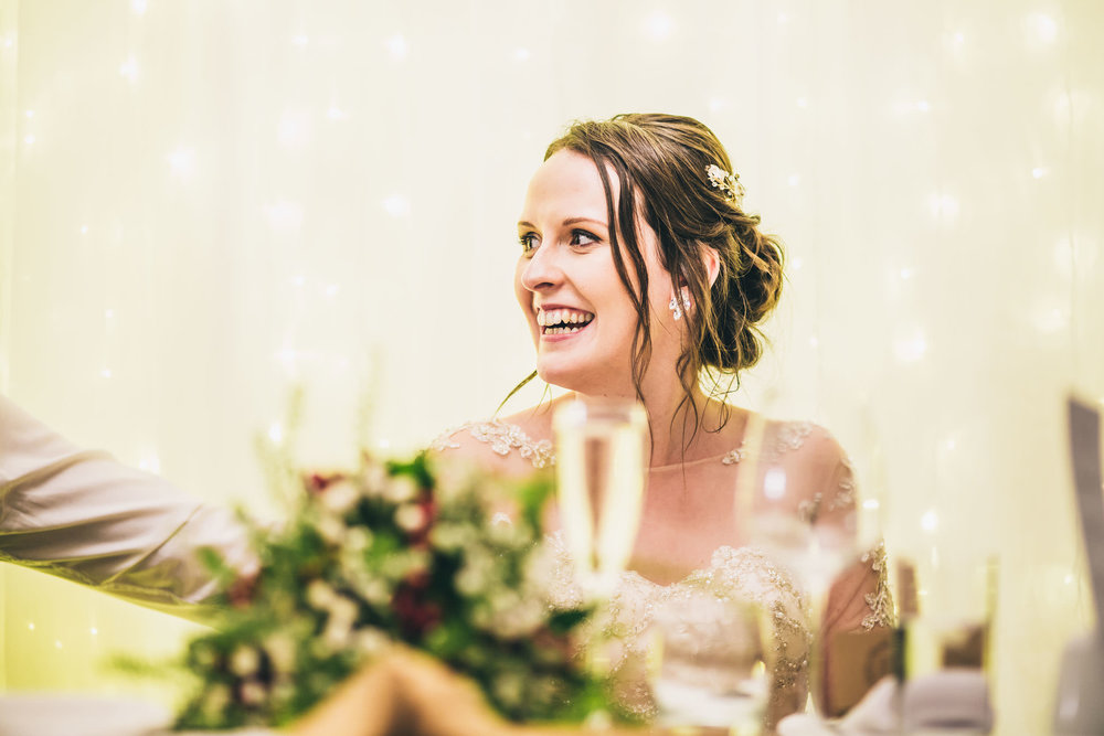 Smiles from the bride during her fathers speech. Creative wedding photographer Lancashire.